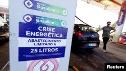 Pengemudi dijatah/dibatasi dalam mengisi bahan bakar di sebuah pompa bensin di Lisabon, Portugal, Senin (12/8).