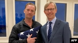 This handout photo released by the US State Department on June 4, 2020 shows US Navy veteran Michael White (L) holding a folded US flag as he poses with US Special Envoy to Iran Brian Hook at Zurich Airport in Zurich, Switzerland, on June 4, 2020,…