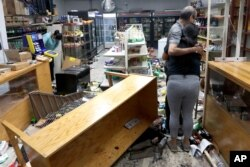 Yogi Dalal abraza a su hija Jigisha luego que su tienda de comidas y licores fue saqueada en la madrugada del lunes.