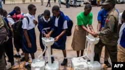 Secondary school students wash their hands at a temporary hand washing point, March 16, 2020. The Rwandan government decided to send home all students of boarding schools after the first case of COVID-19 was found Friday in Kigai.