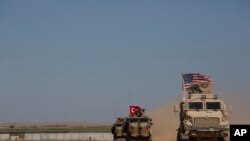 """FILE - Turkish and American forces conduct their first joint ground patrol in the so-called """"safe zone"""" on the Syrian side of the border with Turkey, seen in the background, near Tal Abyad, Syria, Sept. 8, 2019."""