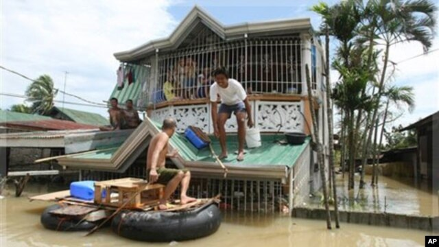 Residents use an improvised raft for transport as floodwaters continue to inundate their homes at Calumpit township, Bulacan province, north of Manila, Philippines, Monday, Oct. 3, 2011.