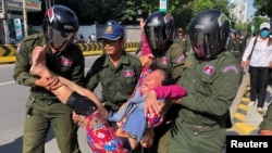 A woman is carried by police officers after security guards broke up a small protest near the Chinese embassy opposing alleged plans to boost Beijing's military presence in the country, in Phnom Penh, Cambodia October 23, 2020. (REUTERS/Heng Mengheang)