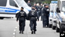 Police investigators secure the streets near the team hotel of soccer team Borussia Dortmund, in Dortmund, Germany, April 12, 2017, a day after their team bus was damaged in an explosion, injuring a player and a police officer.