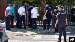 Officials and security personnel stand near the site of reported blast just south of the U.S. Embassy in Beijing, July 26, 2018. A fire or possible explosion appears to have taken place outside the U.S. Embassy in Beijing Thursday.