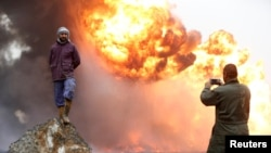 Seorang pria mengambil foto temannya saat asap tebal membumbung dari kebakaran yang terjadi di sumur-sumur minyak yang dibakar oleh kaum militan Islamic State sebelum mereka meninggalkan kawasan produsen minyak Qayyara, Irak (28/1). (foto: REUTERS/Muhammad Hamed)