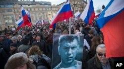 Manifestants tenant un portrait du chef de l'opposition Boris Nemtsov pendant une cérémonie à Moscou marquant le premier anniversaire de son assassinat le samedi 27 février 2016. (AP/ Ivan Sekretarev)
