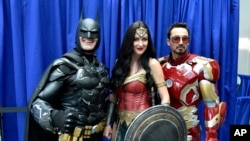 Armando Abarca, dressed as Batman, left, and Jessica Rose Davis, dressed as Wonder Woman, center, of Los Angeles, and Guillermo Gonzalez, of Sacramento, Calif., dressed as Iron Man, attend day one of Comic-Con International on Thursday, July 19, 2018, in San Diego.(Photo by Chris Pizzello/Invision/AP)