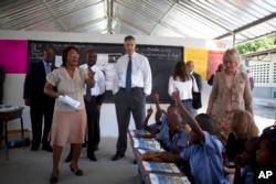 U.S. Secretary of Education Arne Duncan, center, stands in a classroom during his visit to the National School in Tabarre, Haiti, Nov. 5, 2013.