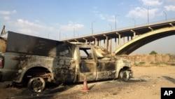 Một chiếc xe của cảnh sát Iraq bị cháy được bỏ lại trên một con đường trong thành phố Mosul