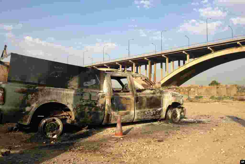 An Iraqi police truck is seen burned on a street in the northern city of Mosul, Iraq, July 6, 2014.
