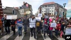 Seorang demonstran memimpin anak-anak berbaris keluar dari distrik Molenbeek dalam unjuk rasa melawan kebencian di Brussels (17/4). (AP/Virginia Mayo)