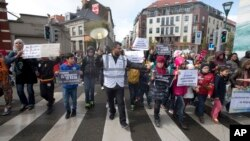An organizer leads children holding signs out of the Molenbeek district during a march against hate in Brussels on April 17, 2016. A new art museum has opened its doors in Brussels' Molenbeek district hoping to help shed the negative image of the area.