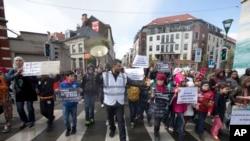 Một người tổ chức dẫn đầu những em nhỏ cầm biểu ngữ đi khỏi khu Molenbeek trong cuộc tuần hành ở Brussels, ngày 17 tháng 4, 2016.