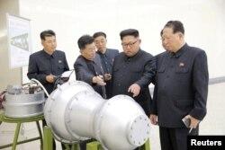 지난 2017년 9월 북한 김정은 국무위원장이 '핵무기 병기화 사업'을 현지지도했다며 관영 조선중앙통신이 공개한 사진. 뒤에 세워둔 안내판에 북한의 장거리탄도미사일 '화성-14형'의 '핵탄두(수소탄)'라고 적혀있다.