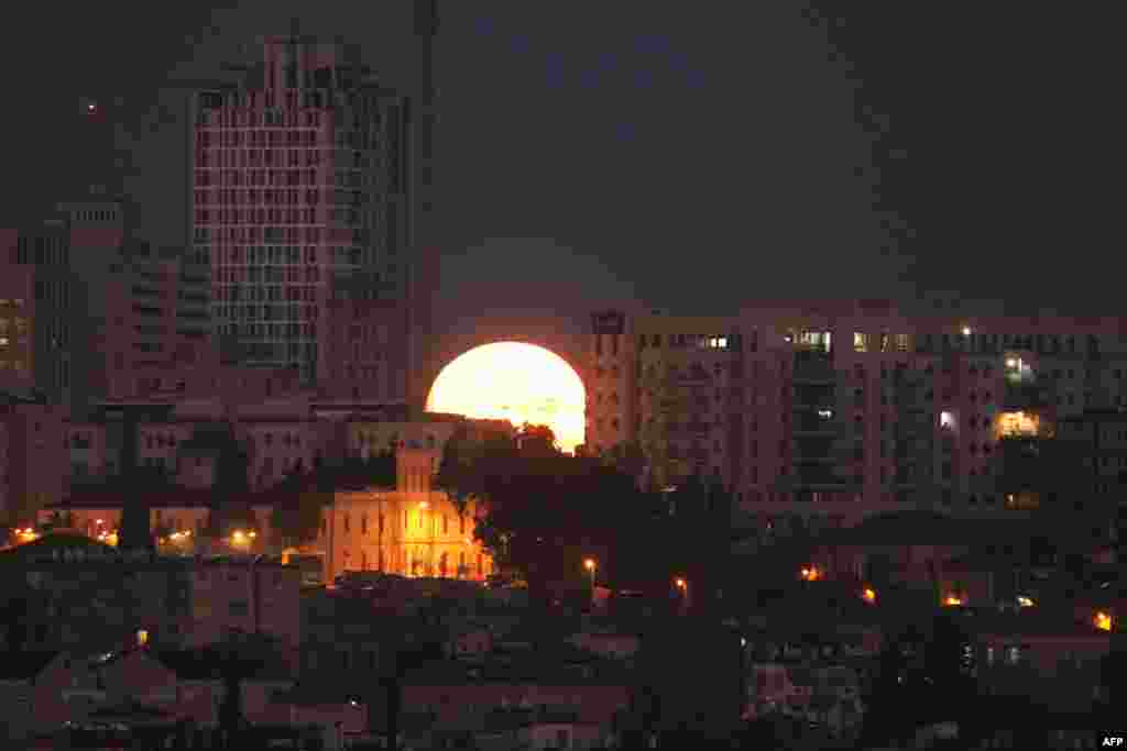 The moon sets behind the city of Jerusalem.
