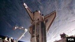 Gambar dari NASA TV ini menunjukkan Discovery merapat di landasan Stasiun Antariksa Internasional, Sabtu (26/2).