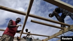 FILE - Workers repair the roof of a holiday resort days after Cyclone Pam in Port Vila, capital city of the Pacific island nation of Vanuatu.