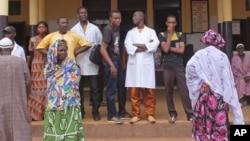 Warga Guinea menunggu kabar anggota keluarga mereka di rumah sakit di di Conakry pasca insiden maut, Rabu (30/7).