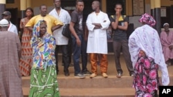 People gather as they await news of friends and family, at a hospital entrance, after a stampede took place Tuesday, during a rap concert, in the city of Conakry, Guinea, July 30, 2014.
