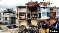 Warga melihat-lihat lokasi bangunan yang hancur akibat gempa di Kathmandu, Nepal (25/4). (Reuters/Navesh Chitrakar)