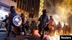香港防暴警察走過一個燃燒的路障去驅散抗議民眾。(2019年11月2日)