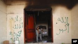 Un hombre mira documentos en el consulado de Bengasi, luego del ataque de septiembre de 2012.