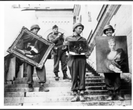 This photo provided by The Monuments Men Foundation for the Preservation of Art of Dallas, shows Monuments Man James Rorimer, with notepad, as he supervises American GI's hand-carrying paintings down the steps of the castle in Neuschwanstein, Germany in May, 1945.