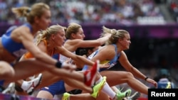 Natallia Dobrynska (R) of Ukraine, leads the field as she competes in her women's heptathlon 100m hurdles heat during the London 2012 Olympic Games at the Olympic Stadium August 3, 2012.