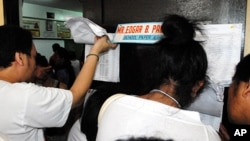 Voters check their papers at a polling station in the Philippine election
