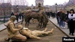 Les Parisiens passent devant une exposition sur le Pont des Arts présentée par le sculpteur Ousmane Sow, le 18 mars 1999.