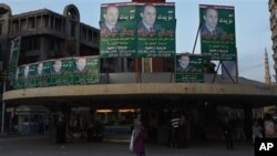 An Egyptian woman walks under electoral posters supporting the ruling National Party with a picture of Gamal Mubarak, son of President Hosni Mubarak, ahead of the upcoming Nov. 28 parliamentary elections, in Alexandria, Egypt, 27 Nov 2010