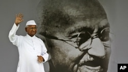 India's anti-corruption activist Anna Hazare waves next to a giant portrait of Mahatma Gandhi on the stage during his hunger strike in New Delhi,India, August 20, 2011