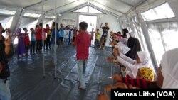 Para relawan dari Komunitas Pecinta Alam Malang Satu Jiwa, Jawa Timur, membawakan sesi pelajaran gempa bumi melalui permainan dan nyanyian di tenda kelas darurat SD Negeri Lolu, Kabupaten Sigi, Sulawesi Tengah, Kamis, 25 Oktober 2018. (Foto: VOA/ Yoanes Litha).