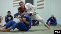 Chris Haueter (in white), one of the well-known BJJ trainers, shows a Jiu Jitsu's technique to a group of expats during a training session at the Olympic Stadium, in Phnom Penh, on February 22, 2016. (Neou Vannarin/VOA Khmer)