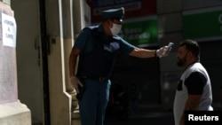 Un agent de sécurité vérifie la température d'une personne à l'extérieur d'un bureau de banque pour s'assurer qu'elle ne présente aucun symptôme du coronavirus.