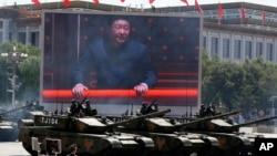参加北京大阅兵的中国坦克部队在显示国家主席习近平的大屏幕前通过。(2015年9月3日)