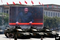 Chinese President Xi Jinping is displayed on a screen as Type 99A2 Chinese battle tanks take part in a parade commemorating the 70th anniversary of Japan's surrender during World War II held in front of Tiananmen Gate in Beijing, Thursday, Sept. 3, 2015.