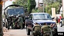 Tentara Madagascar berlindung dari tembakan pemberontak di jalanan ibukota Antananarivo, 20 Mei 2010.
