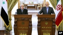 Iranian Foreign Minister Mohammad Javad Zarif, right, speaks in a joint press conference with his Syrian counterpart Walid al-Moallem in Tehran, Iran, Dec. 8, 2014.