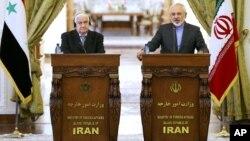 Menlu Suriah Walid Moallem (kiri) dan Menlu Iran Mohammad Javad Zarif mengutuk serangan Israel dalam konferensi pers di Teheran, Senin (8/12).