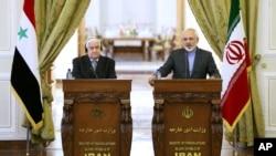 Ngoại trưởng Iran Mohammad Javad Zarif (phải) và Ngoại trưởng Syria Walid al-Moallem trong cuộc họp báo chung ở Tehran, 8/12/14