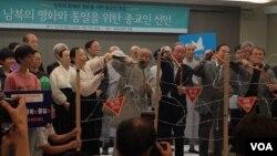 27일 서울 프레스센터에서 열린 '남북의 평화와 통일을 위한 종교인선언' 현장에서 종교인 대표들이 다 함께 철조망을 끊고 있다.