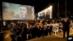 President Barack Obama, on a video monitor, addresses the gathering during a rally in Tel Aviv, Israel, marking 20 years since the assassination of former Israeli Prime Minister Yitzhak Rabin, Oct. 31, 2015.
