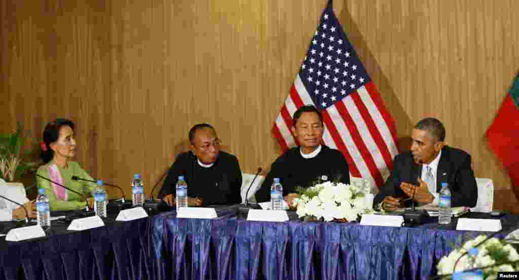 President Barack Obama speaks to Myanmar opposition leader Aung San Suu Kyi (left) during a roundtable with members of parliament and civil society to discuss Myanmar's reform process in Naypyitaw, Myanmar, Nov. 13, 2014.