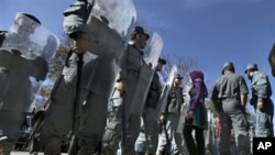 An Afghan woman protester walks past as policemen stand guard during a protest against September's parliamentary poll in Kabul, Afghanistan, 02 Nov. 2010.
