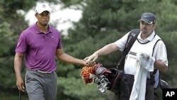 Tiger Woods takes the ball from his caddie Bryon Bell on the first green during first round action at the Bridgestone Invitational golf tournament at Firestone Country Club in Akron, Ohio, August 4, 2011