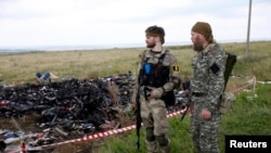 Armed pro-Russian separatists stand guard at the crash site of Malaysia Airlines Flight MH17. (REUTERS July 2014)