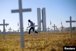 An activist walks past crosses symbolising the ones who died from the coronavirus disease (COVID-19) in front of the National Congress during a protest against Brazil's President Jair Bolsonaro in Brasilia, Brazil June 28, 2020.
