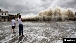 People watch waves hit the shores as Typhoon Usagi approaches in Shantou, Guangdong province, Sept. 22, 2013.